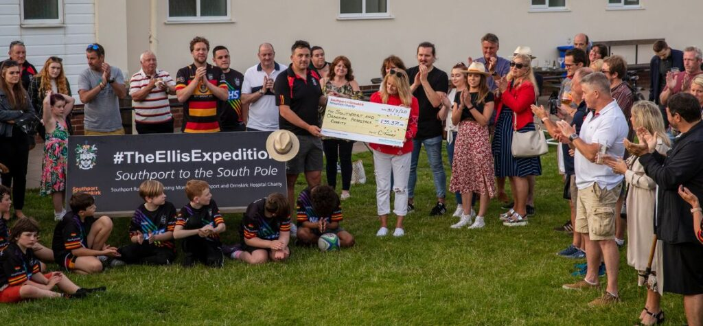 Anne Ellis and Col Toohey and supporters with cheque for over £35,371 raised via The Ellis Exhibition, at Southport Rugby Football Club. Photo by Angus Matheson of Wainwright & Matheson Photography