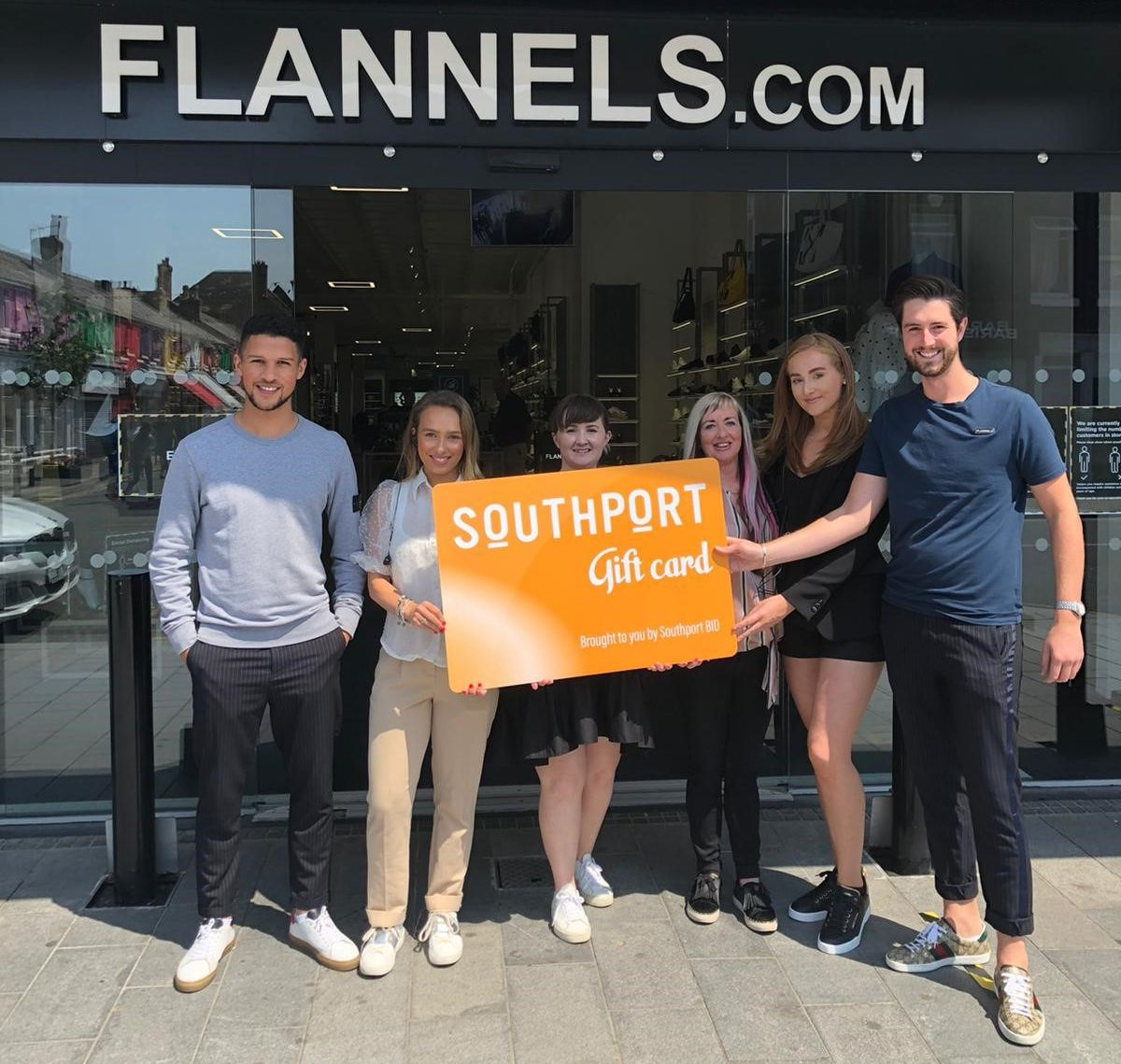 Flannels manager Grant Tindell (right) and staff members welcome the arrival of the brand new Southport Gift Card