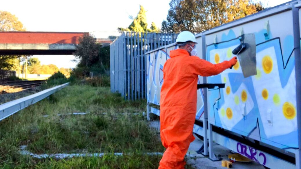 Network Rail workers have been clearing graffiti along the railway line in Southport