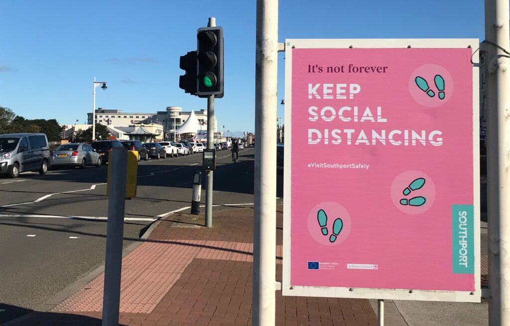 A Covid-19 / Coronavirus warning sign on the Promenade in Southport. Photo by Andrew Brown Media