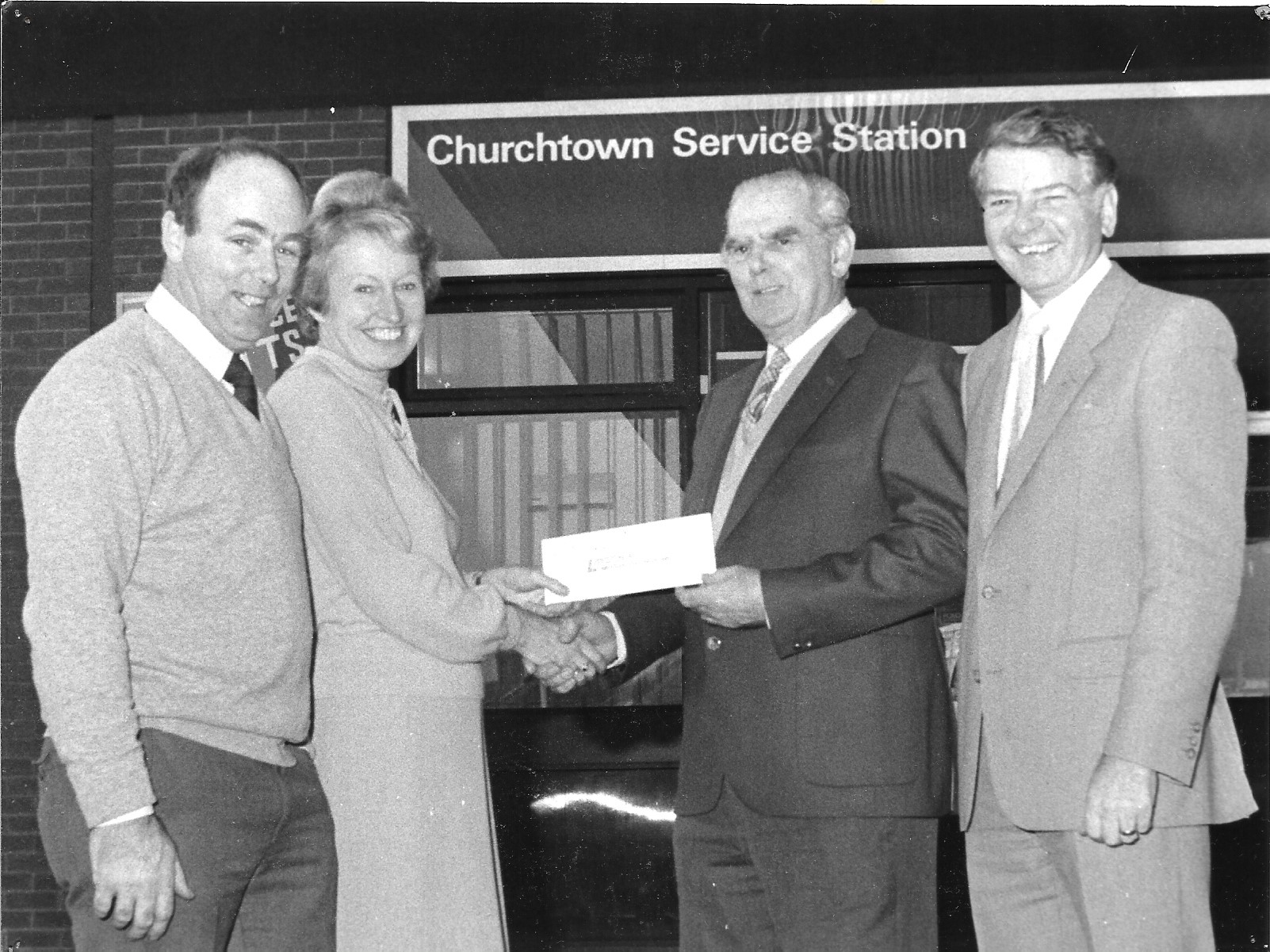 Staff at Churchtown Service Station in Southport present a holiday prize to competition winners on 15 November 1983