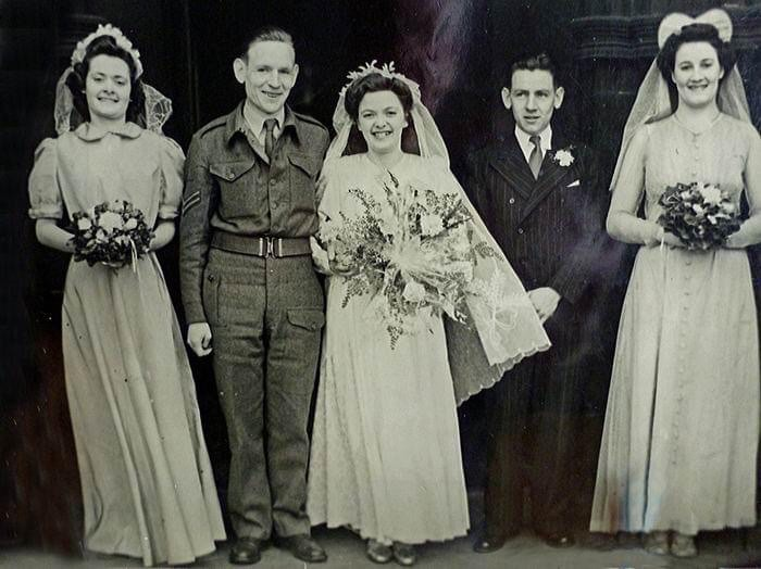 Agnes and Edward Kelly on their wedding day on 23rd March 1945. Everything was rationed. Agnes used a borrowed dress and a cardboard cake, with only one layer real due to egg shortages. The wedding reception was in her parents' house. The piano in the lobby was played by Edward's brother, Harry.